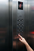 Female hand pressing elevator button going downward