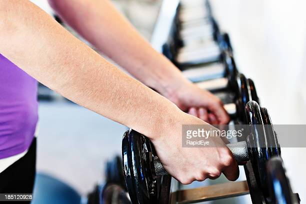 Female hand selects weights from rack in gym