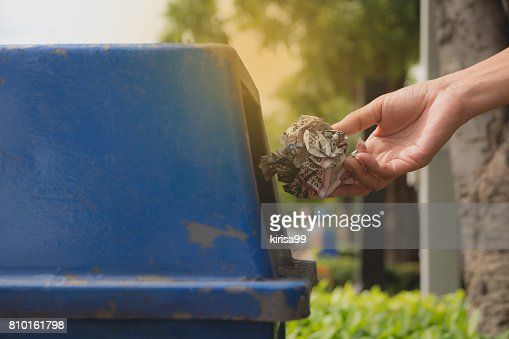 Female hand throwing crumpled paper into blue plastic trashcan. : Stock Photo