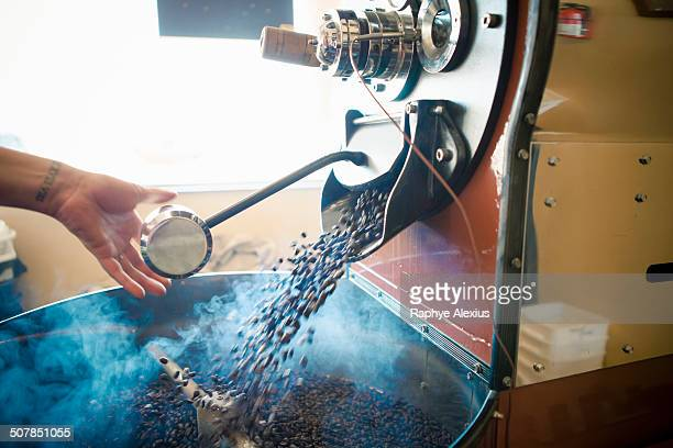 Female hand using industrial coffee roasting machine in cafe