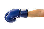 Female hand wearing boxing glove hitting forward or showing isolated on white background with clipping path. Blue boxing glove usually used in training boxers and other combat.