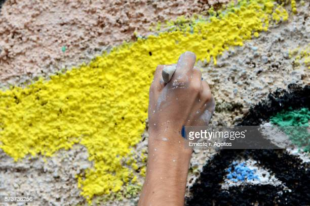 Female hand with a paintbrush painting a rugged wall