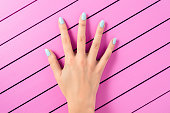 Beautiful female hand with blue nails over pink background