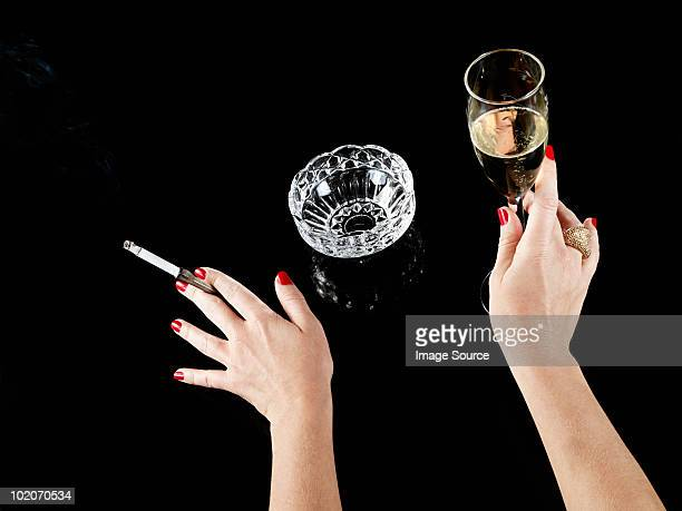 Female hand with cigarette in holder and glass of champagne