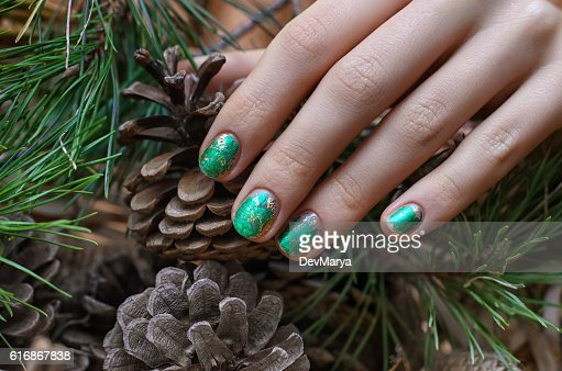 Female hand with green foil nail design : Stock Photo