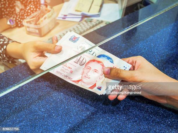 Female hand with money in cash department window. Currency exchange concept. singapore dollar. SGD. cash on counter bank. Hand giving cash and hand receiving cash. payday paying cashier access