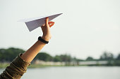 Close-up shot of female hand holding paper plane against sky, picturesque view on background
