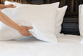 female hands corrected pillow on the bed. Concept on preparation of bed in a hotel room or at home