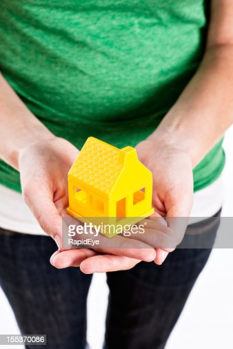 Female hands cradle little yellow house carefully