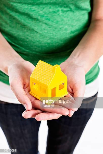 Fêmea mãos suporte pequena casa amarela com cuidado