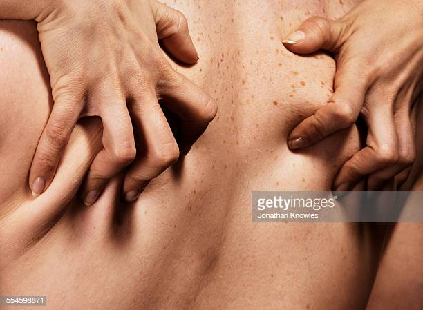 Female hands gripping man's back, close up