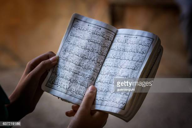 Female hands holding a koran book