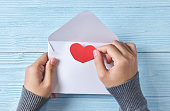 Female hands holding a love letter on blue wooden background. Copy space. Red heart. Top view.