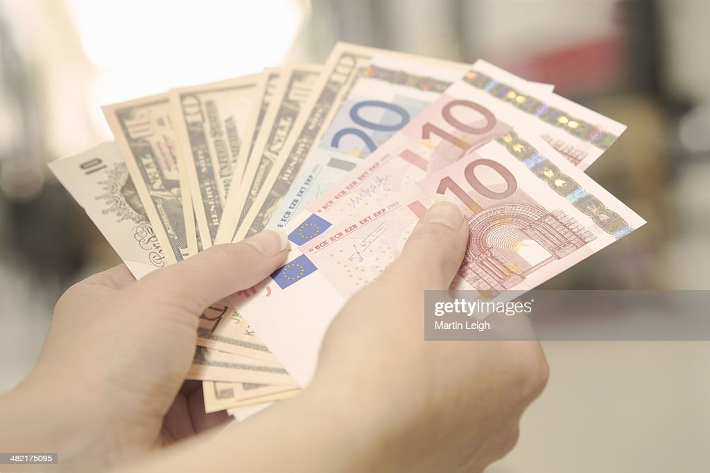 Female hands holding American, British and European bank notes : Stock Photo