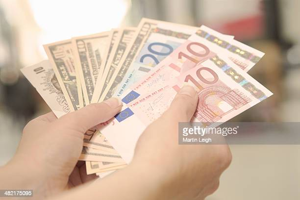 Female hands holding American, British and European bank notes