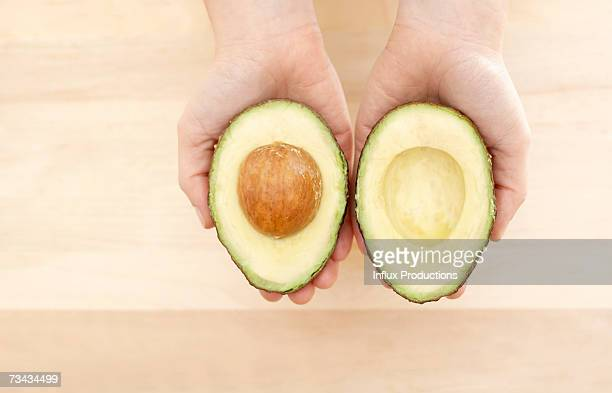 Female hands holding avocado cross-sections, close-up