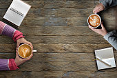 Female hands holding cups of latte art coffee on rustic wooden table background