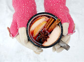 Female hands holding mug of mulled wine with apple and spices. Cup of seasonal hot drink. Homemade fruit tea