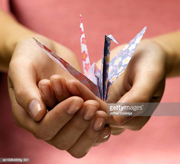 Female hands holding origami crane