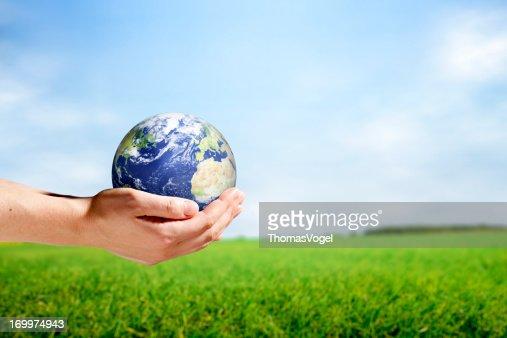 Female hands holding planet earth in rural scene