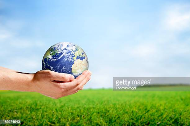Female hands holding planet earth in rural scene
