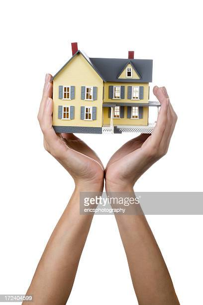 Female hands holding up a yellow model house