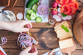 Female hands I collect open sandwiches with rye bread, top view, culinary concept, horizontal