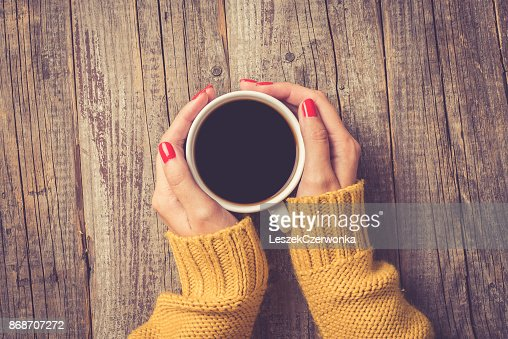 Female hands in warm sweater holding cup of coffee : Stock Photo