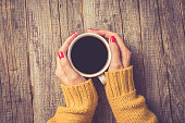Female hands in warm sweater holding cup of coffee. Close up