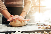 Female hands kneading dough, sunset background. Woman cooking bakery at kitchen table. Homemade cuisine, pastry making, confectionery concept