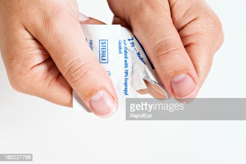 Female hands open sterile swab used to disinfect skin