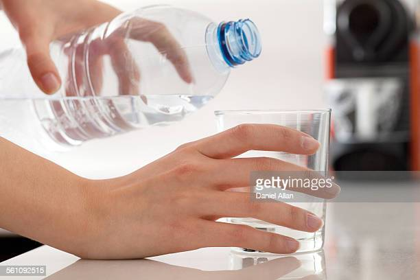 Female hands pouring bottled water into glass