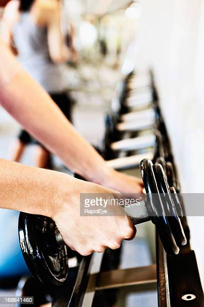 Female hands selecting weights from rack in a gym