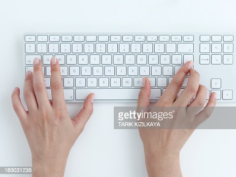 Female hands typing on a white computer keyboard