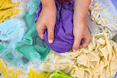 Female hands wash colored clothes in basin.