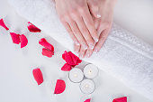 Beautiful young female hands with french manicure modern style on towel with red rose petals and candle in beauty salon. Manicure and Beauty concept. Close up, selective focus