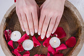 Beautiful female hands with french nails polish style and wooden bowl with water and floating candles and red rose petals. Manicure and Beauty concept. Close up, selective focus