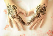 Beautiful drawing henna on female hands with mehndi decoration in heart shape. Love Concept.
