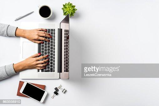 Female hands working on modern laptop. Office desktop on white background : Stock Photo