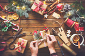 Female hands wrapping christmas holiday handmade presents in craft paper with ribbon on wooden table. Top view