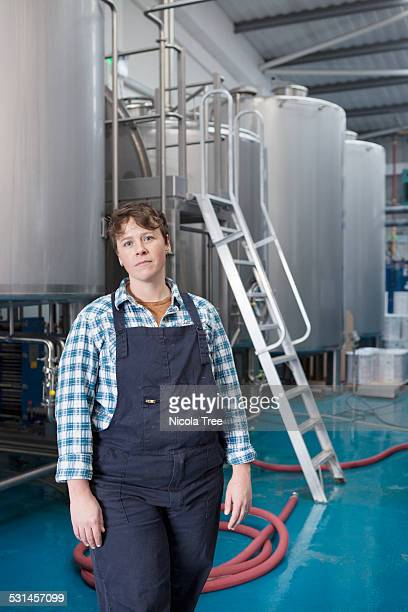 Female head brewer standing in front of brewery