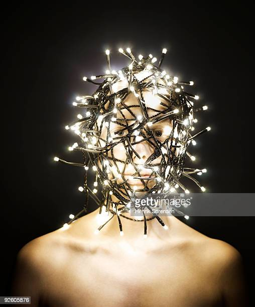 Female head wrapped in lit fairy lights