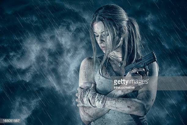 Female heroine holding pistol in rain
