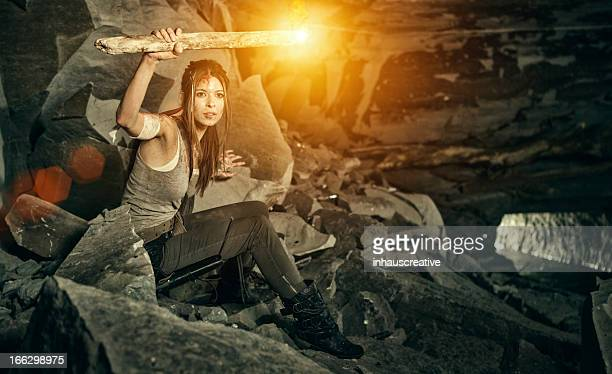 Female heroine looking in a cave with torch