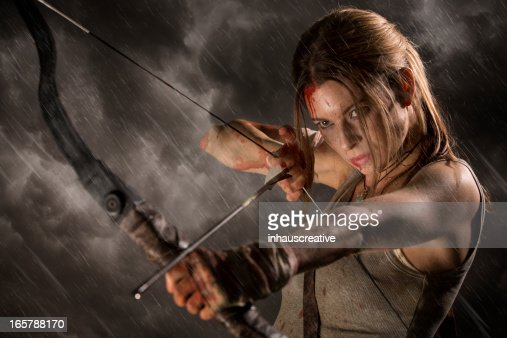 Female heroine with bow and arrow on a rainy night
