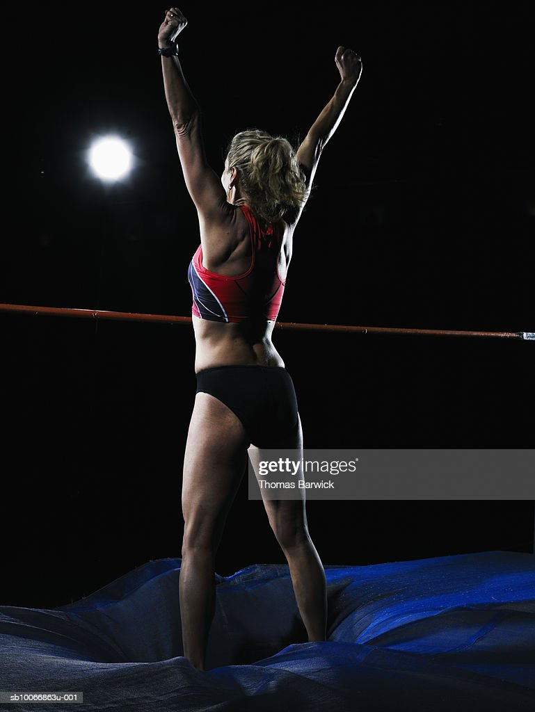Female high jumper celebrating, arms up : Stock Photo