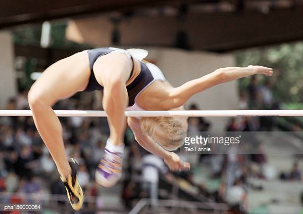Female high jumper clearing bar, low angle view