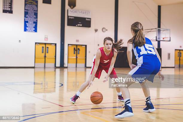 Female high school basketball player dribbling to hoop