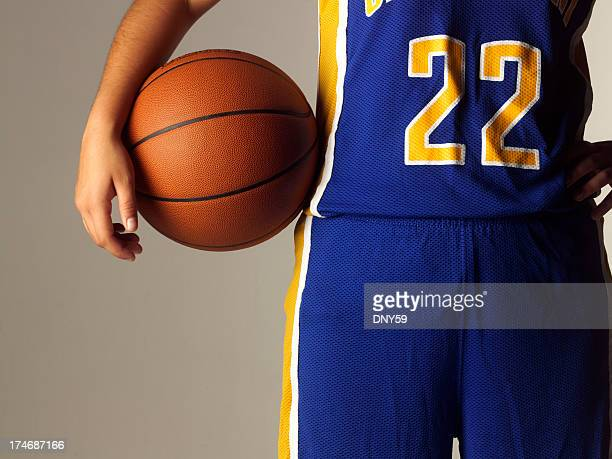 Female high school or college basketball player holding basketball