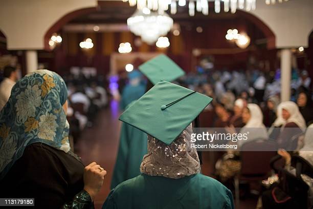 Female high school seniors wear a traditional cap and gown while attending their high school graduation ceremonies from the al Noor School June 23...